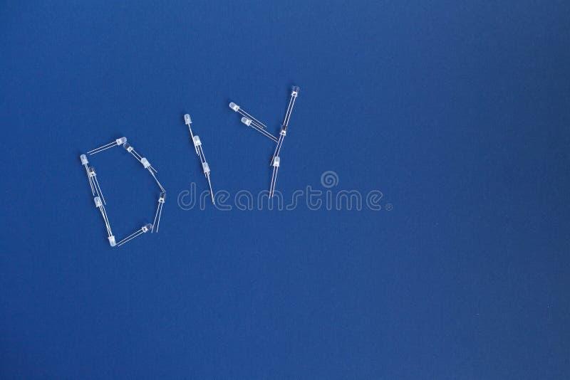 DIY-woord van diode op blauw een achtergrond DIY-de woorden voor doen het zelf concept Plaats voor tekst stock foto