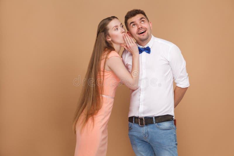 Dizendo uma mulher loura secretBeautiful no vestido cor-de-rosa que diz o segundo imagens de stock