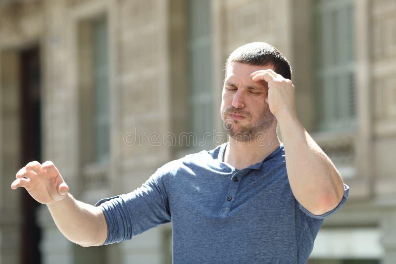 Dizzy adult man suffering headache in the street stock image
