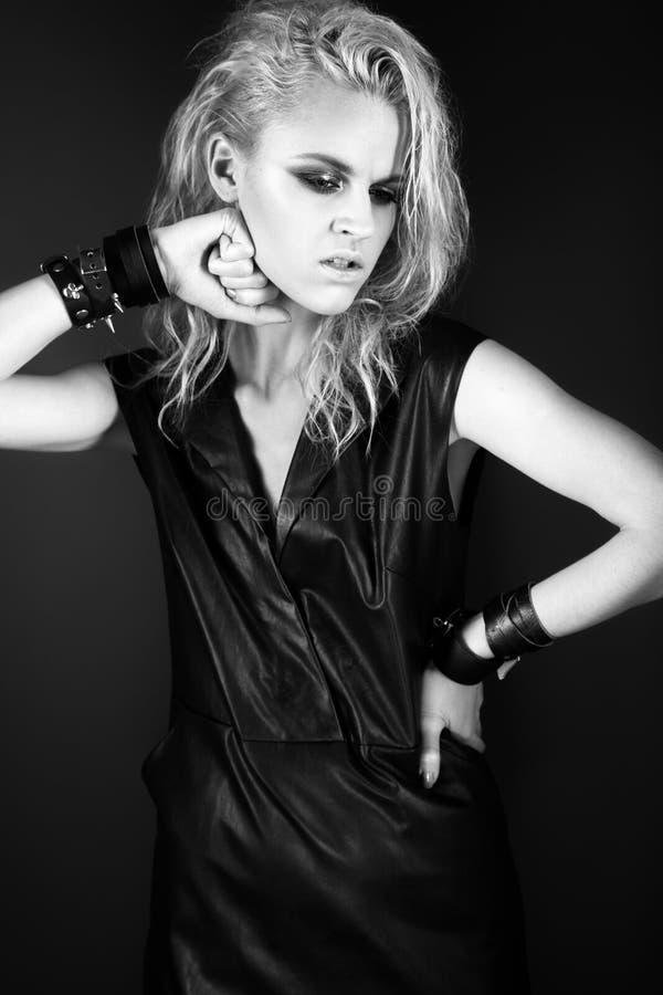 Djärv flickamodell i svart läderklänning, stil av arkivfoto