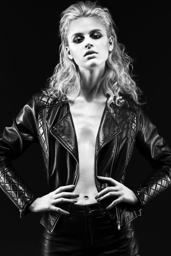 Djärv flickamodell i svart läderklänning, stil av arkivbilder