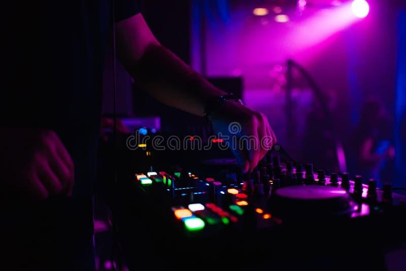 DJ在移动在音乐委员会的夜总会控制音乐控制器 库存图片