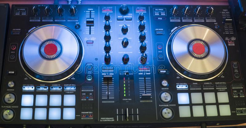 DJ戏剧和混合音乐在数字式搅拌器控制器 特写镜头DJ表现控制器,数字式密地转盘系统 免版税库存图片