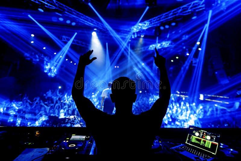 DJ手在蓝色光下的夜总会党与人人群  免版税库存照片