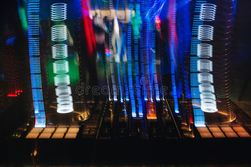 DJ搅拌器在有发光的色的光的一个夜总会从控制器和按钮 库存照片