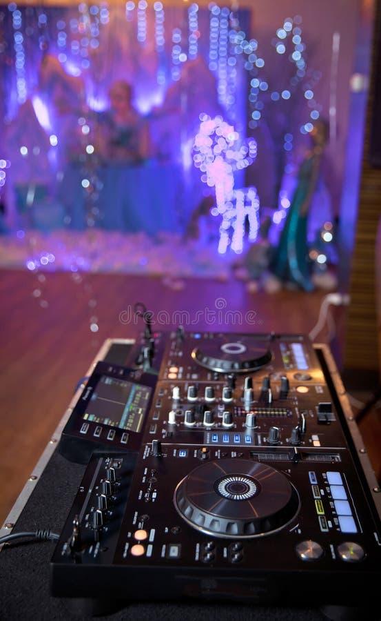 DJ的特写镜头手佩带在白色衬衣的控制板的 使用在专业设备的音乐节目主持人在夜总会 库存图片