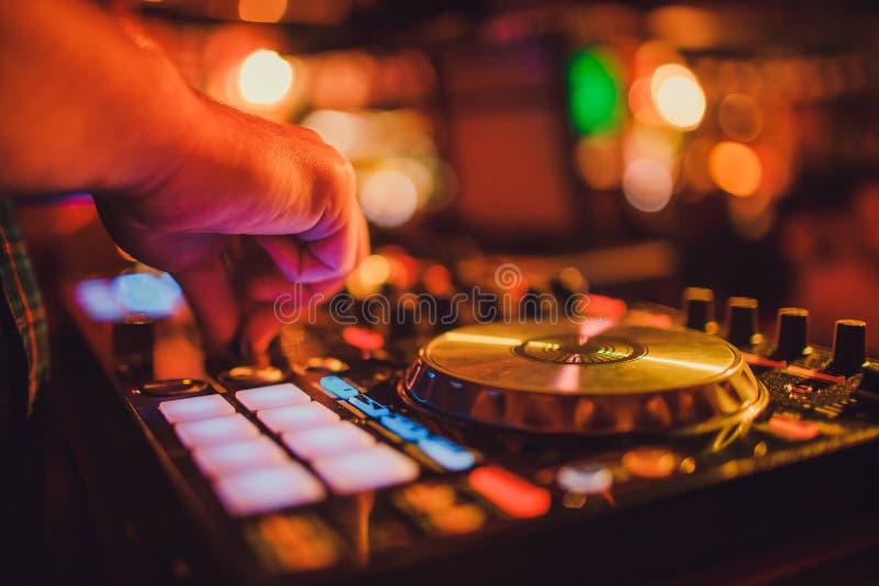 DJ遥控、转盘和手 在俱乐部的夜生活,党 库存照片