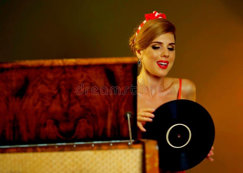 dj音乐减速火箭的转盘葡萄酒乙烯基妇 女孩穿红色礼服的画报样式 免版税图库摄影