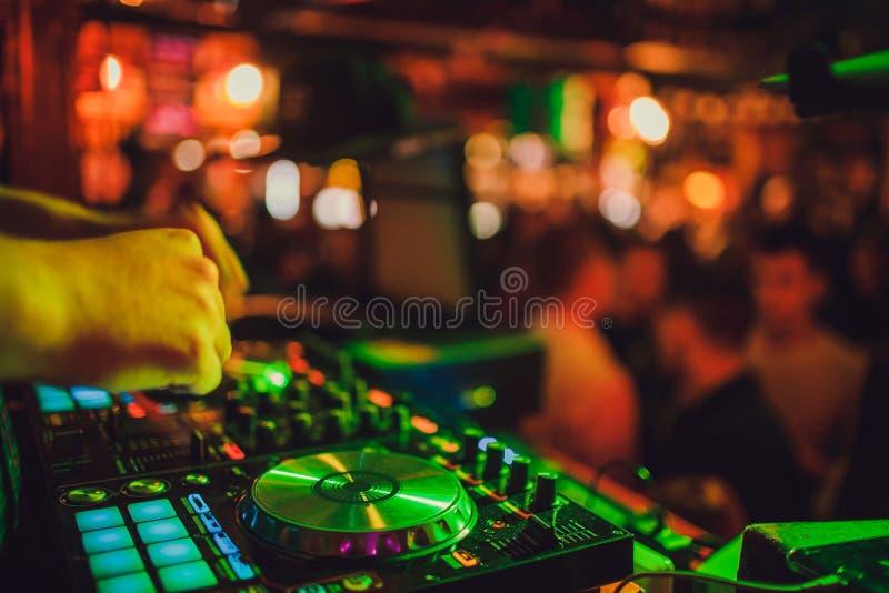 DJ μακρινό, περιστροφικές πλάκες, και χέρια Ζωή νύχτας στη λέσχη, κόμμα στοκ φωτογραφίες