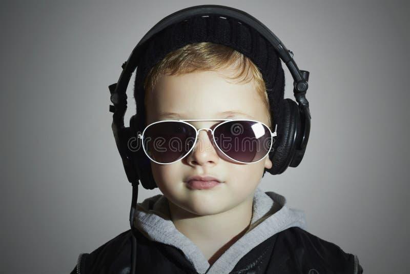 dj немногая смешной мальчик в солнечных очках и наушниках нот наушников ребенка слушая диск-жокей стоковая фотография