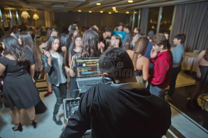 DJ с наушниками на партии ночного клуба под красочной толпой света и людей в предпосылке Dj на открытой партии aire Партия ночи стоковая фотография rf
