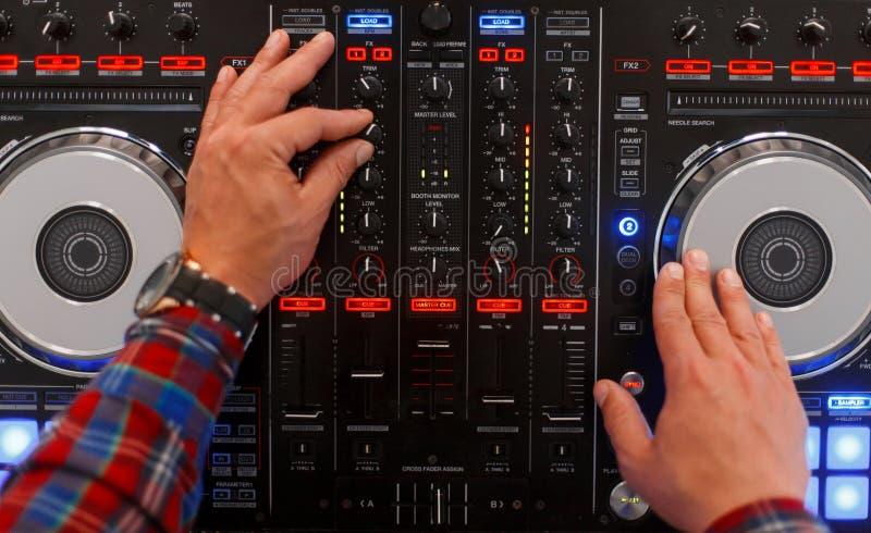 DJ укомплектовывает личным составом игры на музыкальном оборудовании Взгляд сверху стоковая фотография