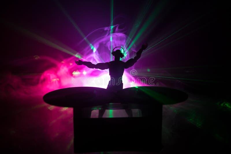 E 混合和抓在夜总会的DJ 在乙烯基转盘、闪光灯光和雾的人剪影在背景 图库摄影