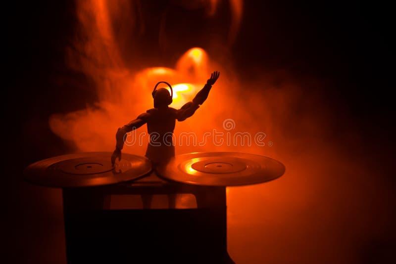 E 混合和抓在夜总会的DJ 在乙烯基转盘、闪光灯光和雾的人剪影在背景 免版税库存图片