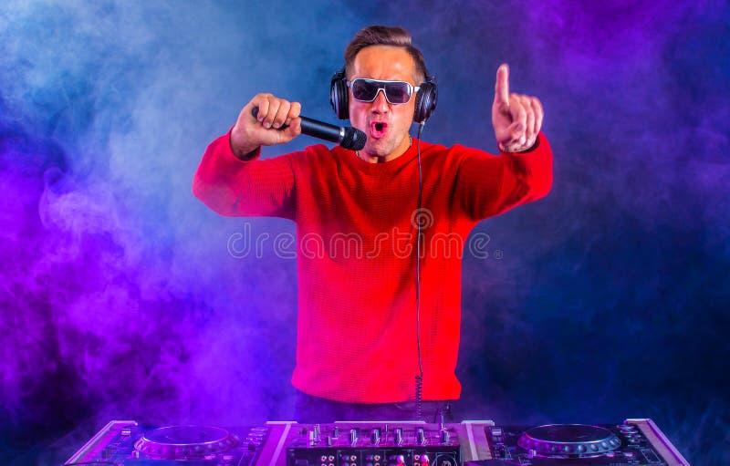 DJ actif avec microphone dans la discothèque photographie stock