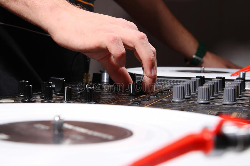DJ adjusting soiund level on mixing controller. Hand of a DJ mixing track on vinyl records. Volume adjustment is in progress stock images