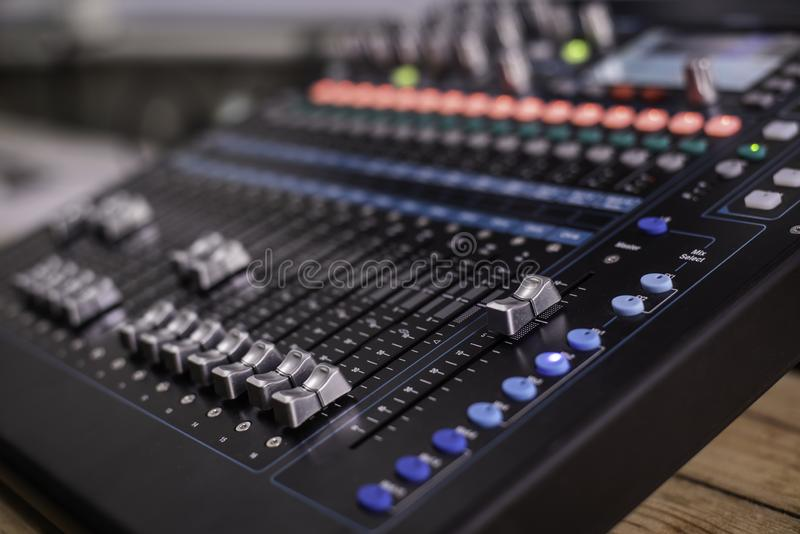 The DJ is adjusting the volume of the sound. Professional audio. Mixing console royalty free stock photos