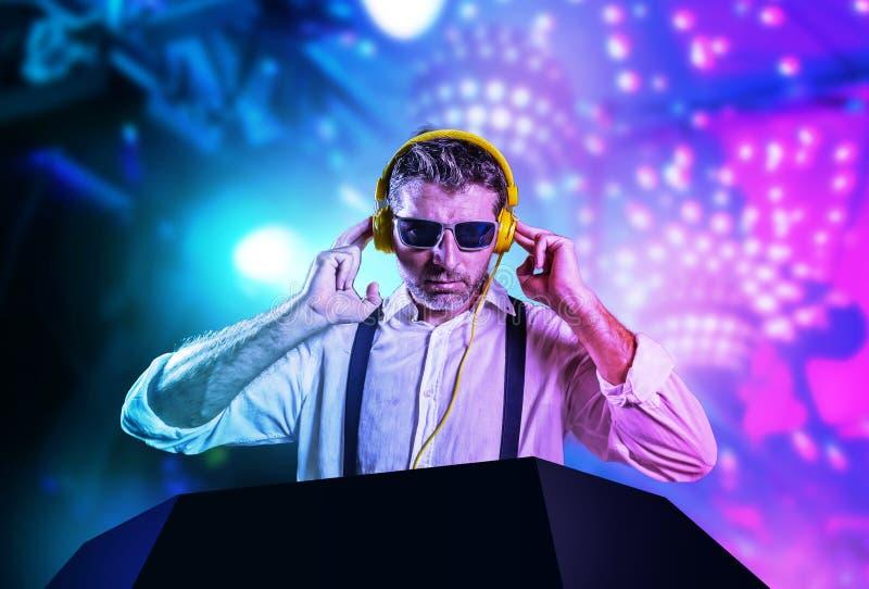 DJ atrativo e fresco novo na camisa e nos suspensórios que remixing a música no clube noturno que usa fones de ouvido no strobo imagem de stock