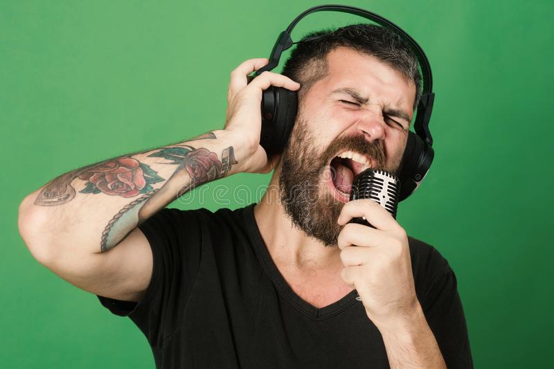 Dj with beard wears headphones. Man sings on green background. Singer with beard and excited face listens to music. Relax and music concept stock image