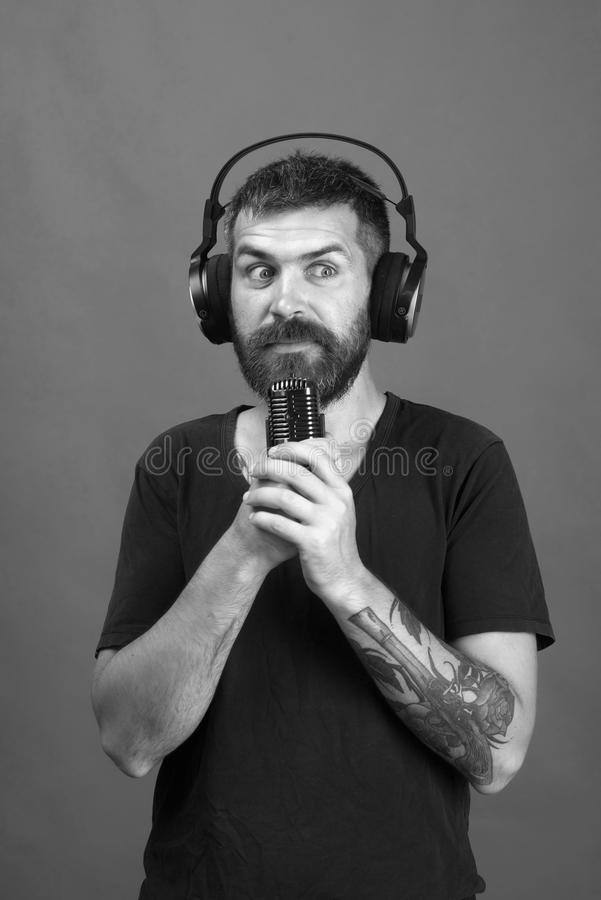Dj with beard wears headphones. Singer with beard and shocked face listens to music. Man holds microphone on green. Technologies and music concept. Dj with beard royalty free stock image