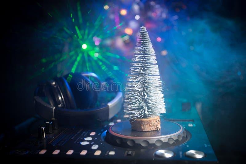 Dj-blandare med hörlurar på mörk nattklubbbakgrund med helgdagsafton för nytt år för julgran Nära övre sikt av beståndsdelar för  fotografering för bildbyråer