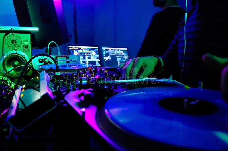 DJ Booth and Equipment, Rave Nightclub Music, Colorful Lights,. DJ booth equipment lighted in blue. Red, yellow, green and white lighted buttons. Light jockey royalty free stock photos