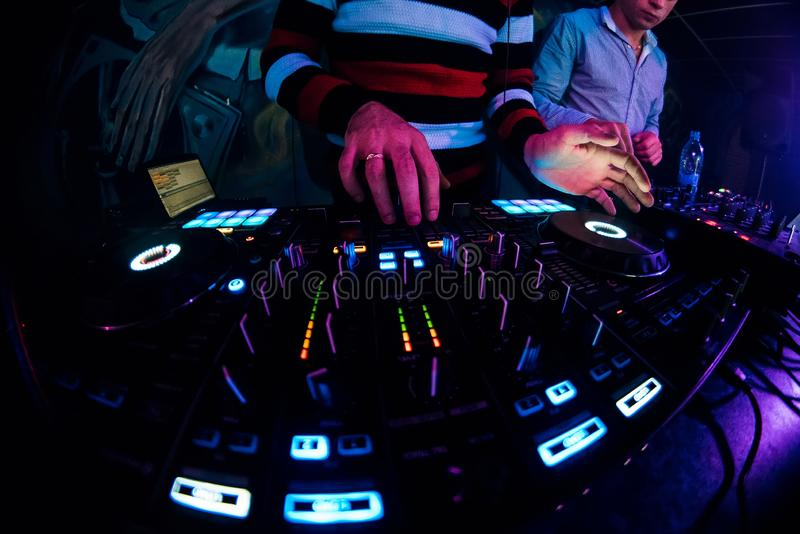 DJ in a booth playing a mixer at a nightclub stock photo