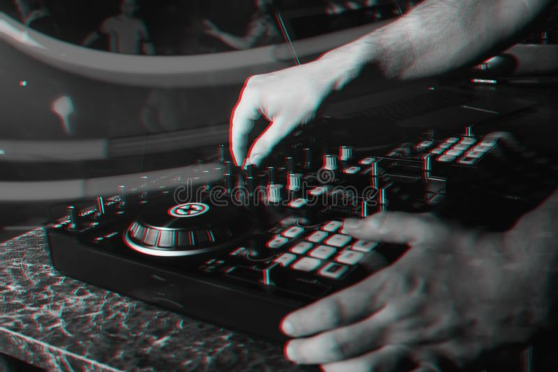 DJ in booth playing in nightclub on background of mixer. DJ in the booth playing in a nightclub on the background of the mixer. Black and white photo with glitch royalty free stock photography