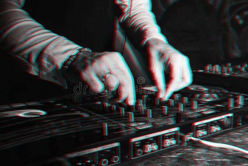 DJ in booth playing in nightclub on background of mixer. DJ in the booth playing in a nightclub on the background of the mixer. Black and white photo with glitch stock image