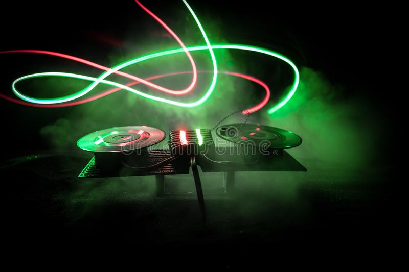 Dj club concept. Creative artwork decoration of dj table on dark toned background with lights and fog royalty free stock photo