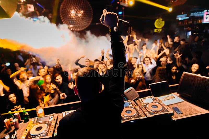 DJ at club. A disc jockey playing to a club full of people dancing and cheering stock photos
