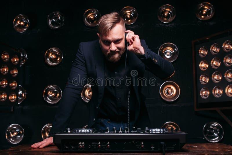 DJ com fones de ouvido e misturador que verificam o equipamento imagens de stock