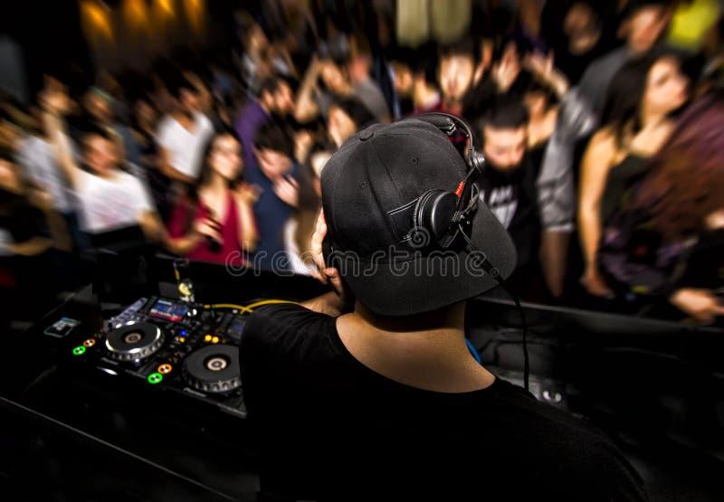 DJ con el auricular y DJ fijaron en el club de noche fotografía de archivo