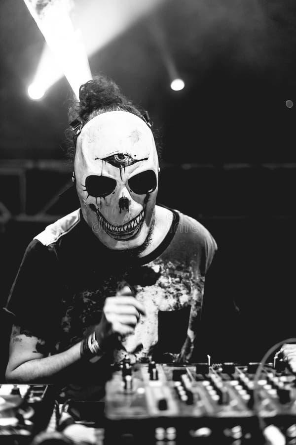 DJ con el cráneo enmascara jugar música electrónica en el festival del partido del verano foto de archivo libre de regalías
