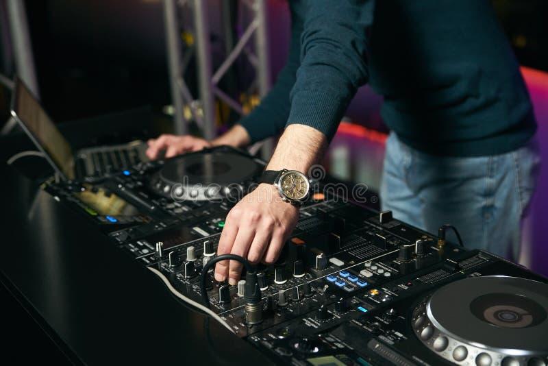 DJ con las placas giratorias que juegan música en el mezclador fotografía de archivo