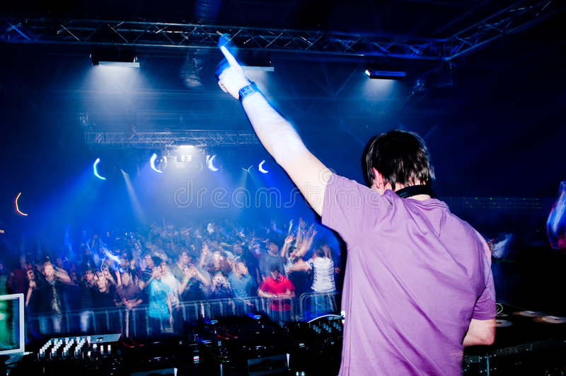 Dj at the concert. Blurred crowd on background stock photo