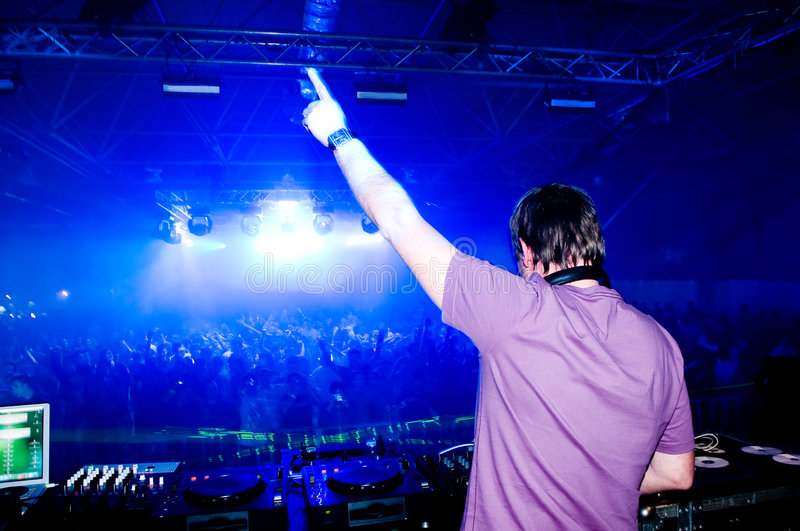Dj at the concert. Blurred crowd on background royalty free stock photo