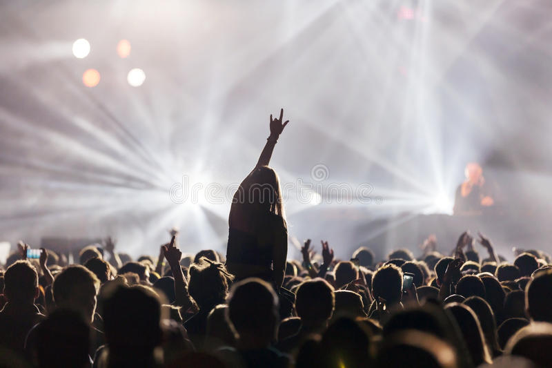 Dj at concert. Concert, disco party. Woman silhouette with hand up in foreground and people having fun stock photos