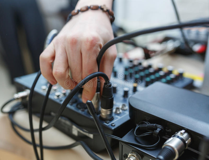 DJ connects the sound equipment for the event or party. Man`s hand holding the audio connector on the background of the sound equipment stock photos