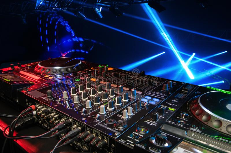 DJ console in the atmosphere of the party, light spotlights. Scene fragment royalty free stock photos