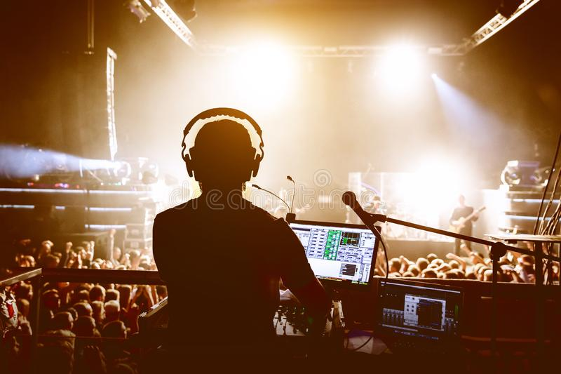 DJ with crowd of people in night club party under stage light stock images