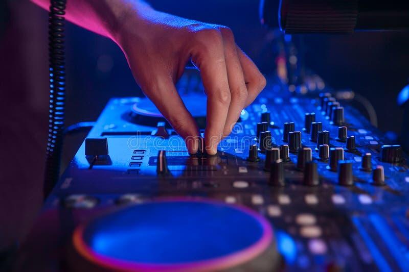 DJ da en regulador de mezcla en luz azul primer imágenes de archivo libres de regalías