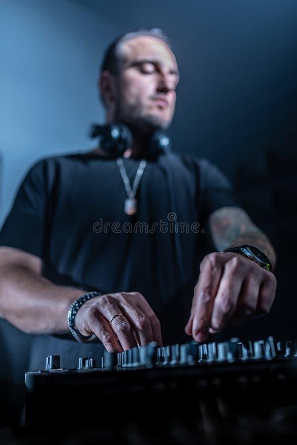 DJ, das Haus- und technomusik in einem Nachtklub spielt Die Musik mischen und steuernd lizenzfreie stockfotografie