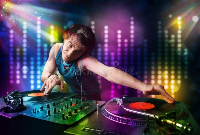 DJ, das Lieder in einer Disco mit heller Show spielt stockfoto