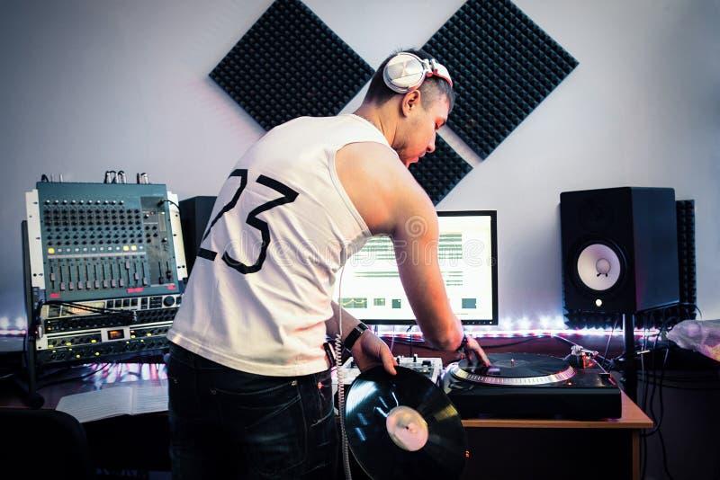 DJ, das mit mischender Platte am Studio arbeitet lizenzfreies stockbild