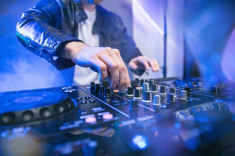 DJ, das am Parteifestival mit Blaulichtern und Rauche im Hintergrund mischt stockfoto