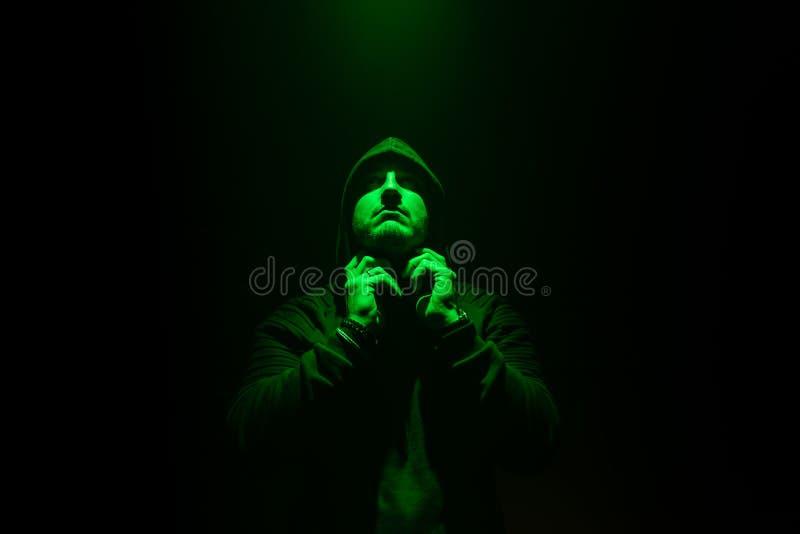 DJ, das seine Kopfhörer oder an in eine Dunkelkammer beseitigt Grünes Licht auf Gesicht lizenzfreies stockfoto