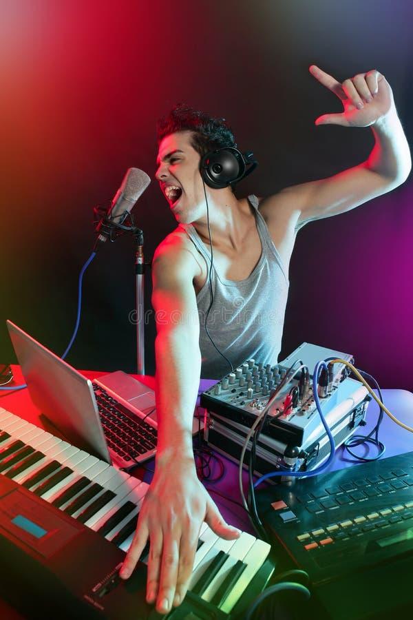 DJ dat met kleurrijke licht en muziek apparatuur mengt stock foto's