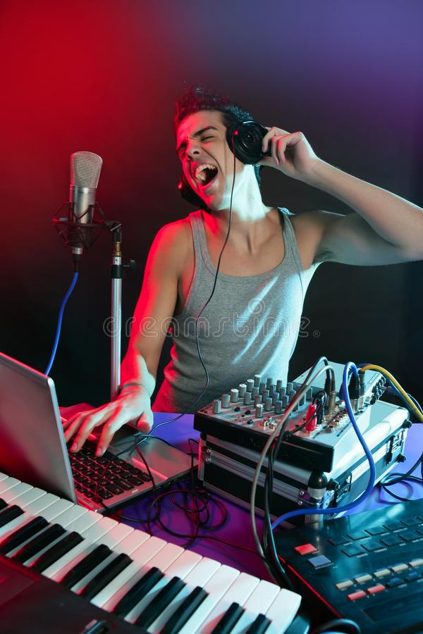 DJ dat met kleurrijke licht en muziek apparatuur mengt stock foto