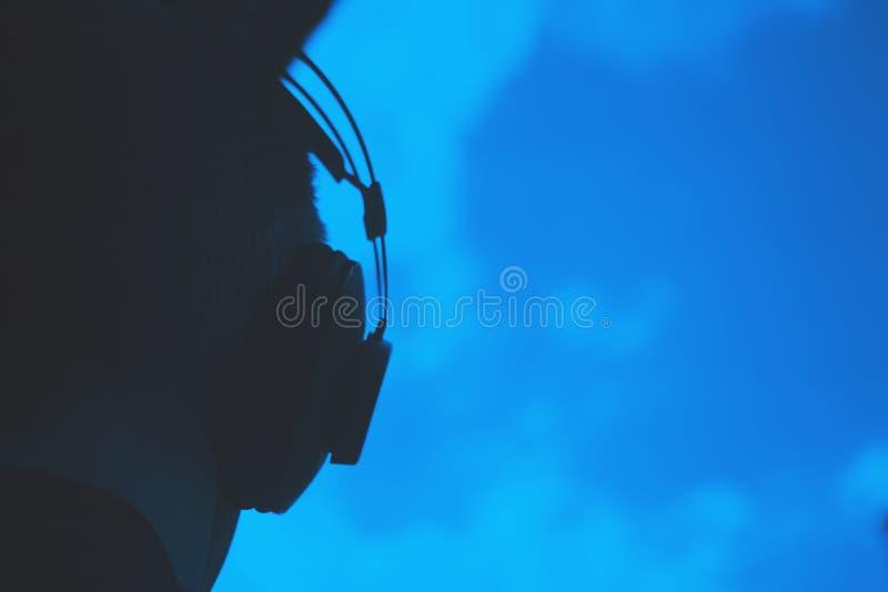 DJ deejay producer wearing headphones. DJ deejay producer wearing closed headphones listening to music in artistic photo stock photography